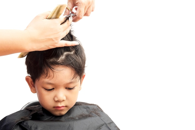 少年は白い背景で隔離された髪のドレッサーによって彼の髪をカットします。