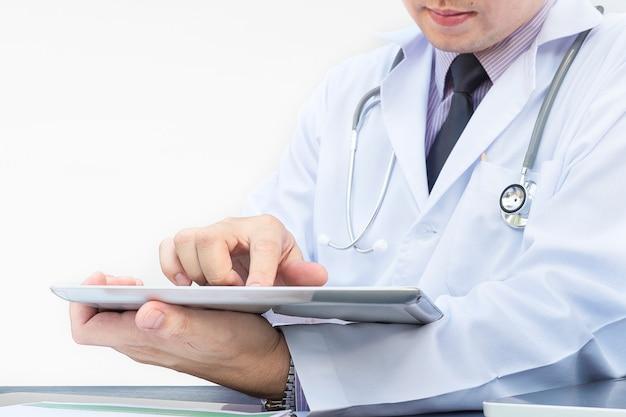 医者は白い背景の上のタブレットで働いています。