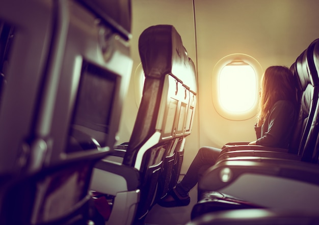 女性は窓から光沢のある太陽を見て飛行機に座っています。