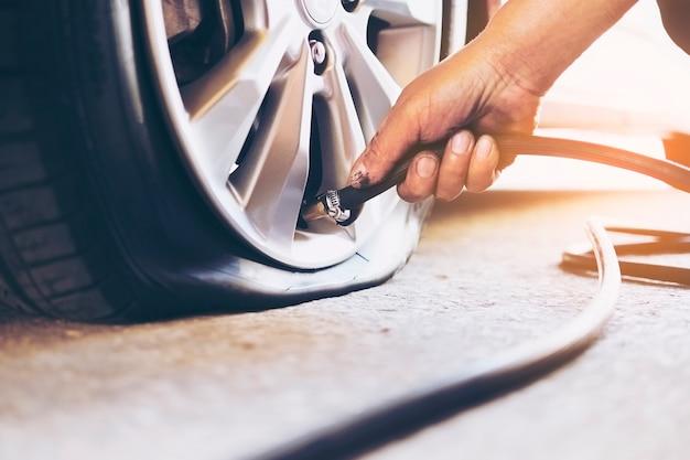 技術者は車のタイヤを修理しています