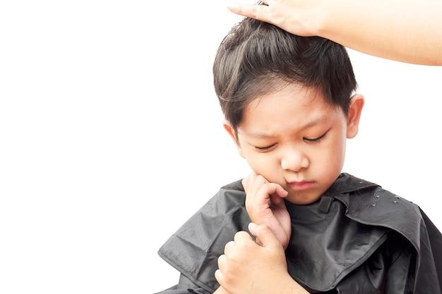 少年は白い背景で隔離されたヘアドレッサーで彼の髪をカットしながらかゆみを感じています。
