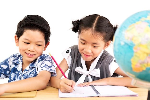 アジアの子供たちは白い背景の上にぼやけた地球で楽しく勉強しています。