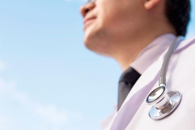 男性医師は青い空を見ています。医療サービスの未来のための概念
