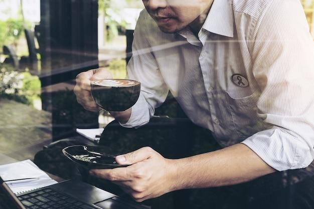 ビジネスマンはコーヒーショップで彼のコンピューターで働いています。