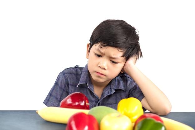 アジアの少年は白い背景の上に嫌いな野菜の表現を見せています。