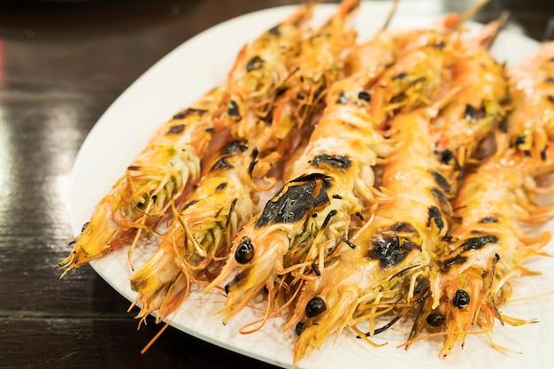 焼きエビのレシピは木製のテーブルの上の白い皿に役立ちます