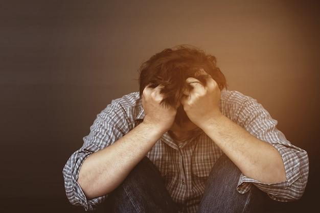 Печальный мужчина держит голову рукой