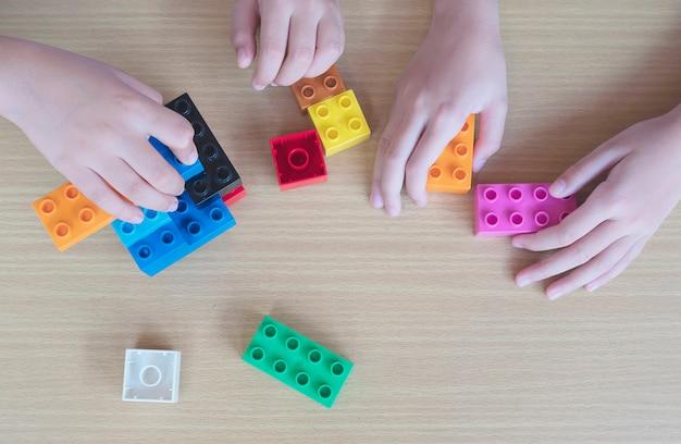プラスチック製の創造的な建設ブロックを遊んでいる子供たち