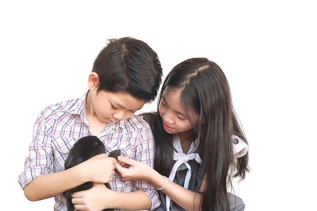 Мальчик и девочка играют с маленьким кроликом