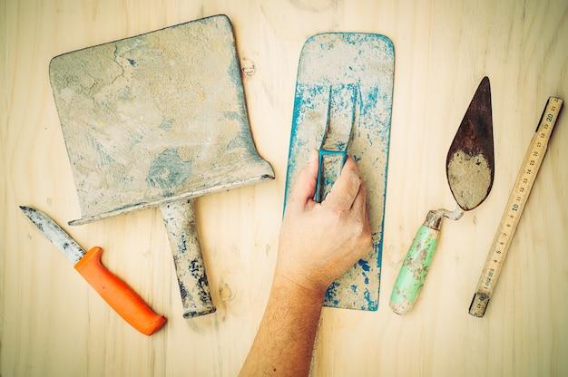 白い木製の背景上の労働者の手で古い建設手のひらツール