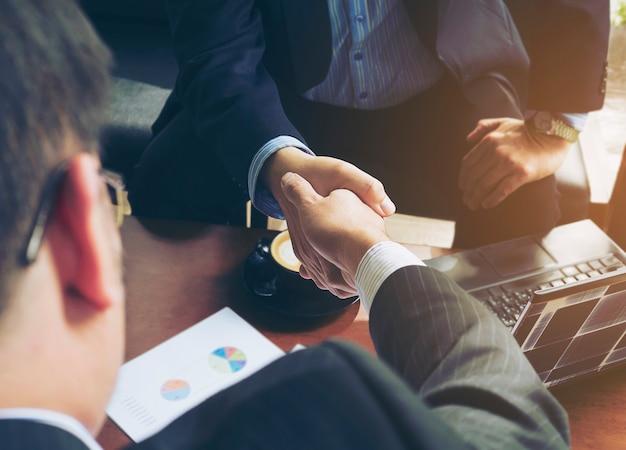 Два бизнесмена пожать руку в кафе