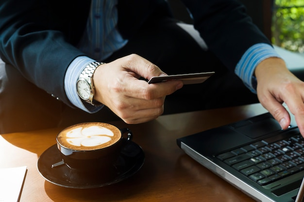 クレジットカードを使用してコーヒーショップでオンライン商品を購入するビジネスマン