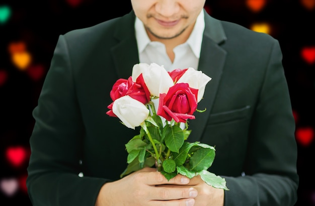 バレンタインの日に誰かに赤と白の花束のバラを与える男
