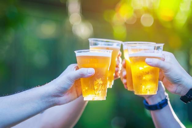 お祝いビール応援コンセプト - 人々のグループのビールのグラスを両手を閉じる