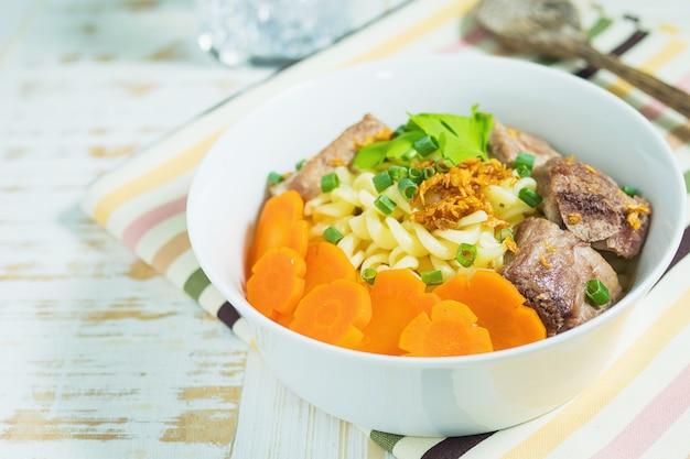 豚肉とニンジンの白い木製のテーブルの上のマカロニスープ