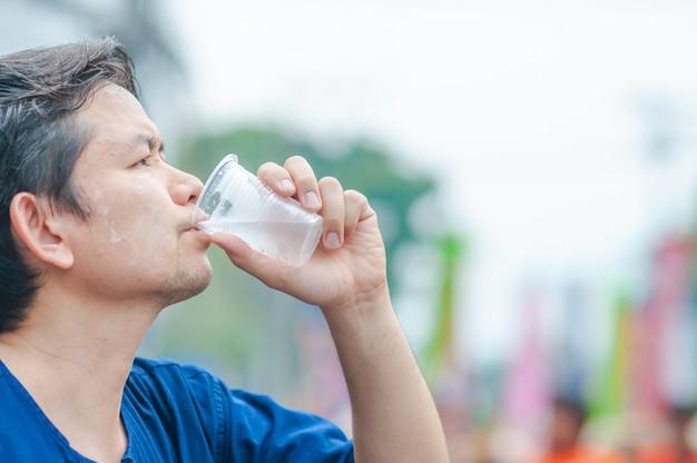 Северный тайский мужчина пьет свежую холодную воду в пластиковом стакане во время участия в мероприятиях на свежем воздухе