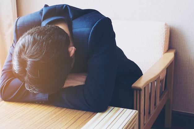 ホテルの部屋に座っている悲しいビジネスマン