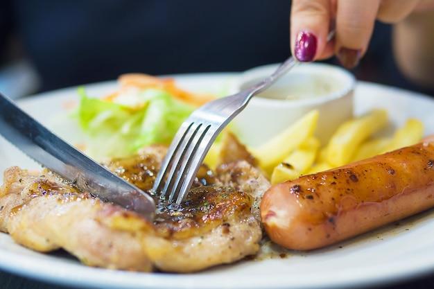 Люди бросают соус к куриному стейку с колбасой, картофелем фри и салатом