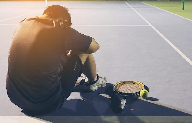 Грустный теннисист сидит на корте после проигранного матча