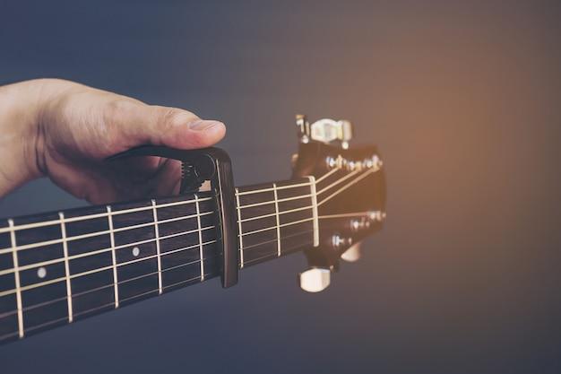 灰色の背景上にギターのカポを置く男のビンテージカラー写真