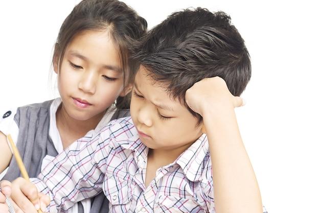 子供は白い背景の上に一緒に宿題をやっています。