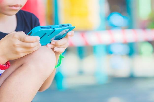 子供はカラフルな背景を持つ携帯電話でゲームをプレイします。
