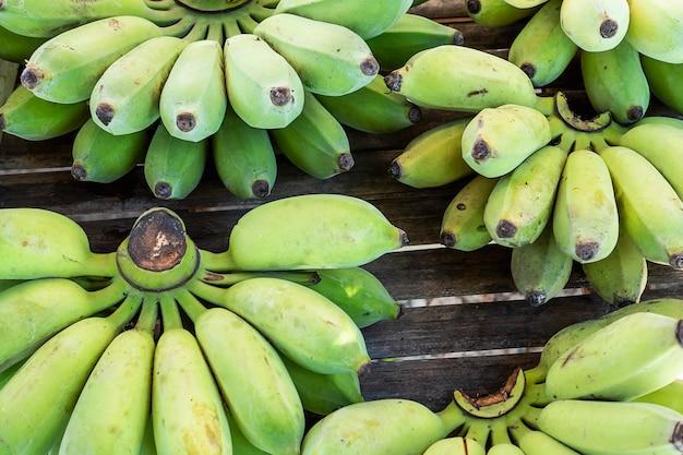 新鮮な緑の有機バナナ手のタイのローカル市場での販売の準備ができて