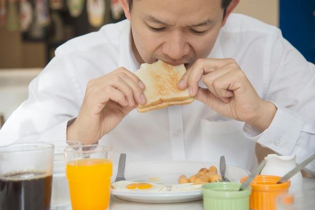 ビジネスの男性がホテルで設定したアメリカンブレックファーストを食べる