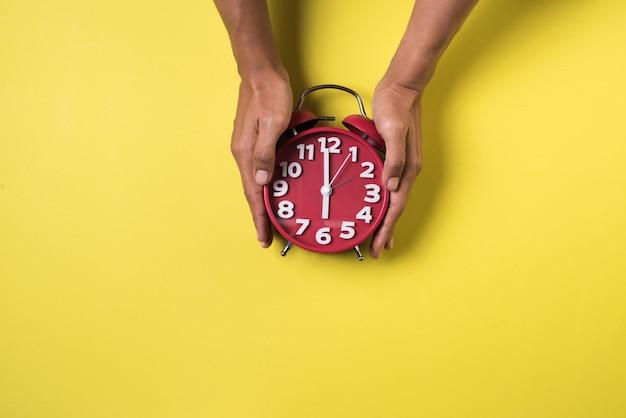 トップビューの手と目覚まし時計