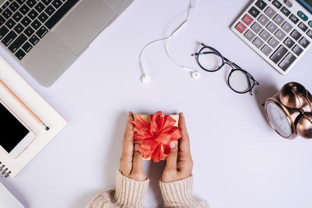 Вид сверху рука подарочной коробке на рабочем месте
