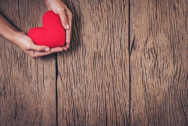 木材の背景に赤いハートを持っている手