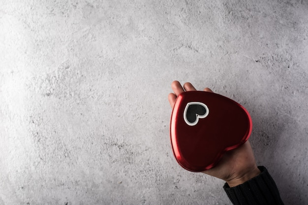 Вид сверху рука держит красное сердце на фоне стены