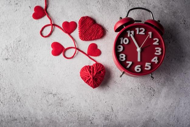 赤いハート、バレンタインの日の概念と赤い目覚まし時計。