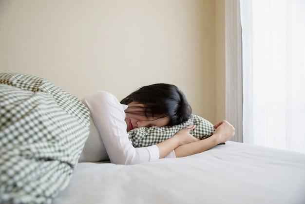 女性は幸せに眠り、朝は清潔なベッドルームで落ち着きます