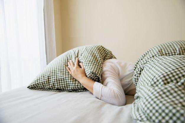 女性はベッドの上に枕で彼女の頭をカバー