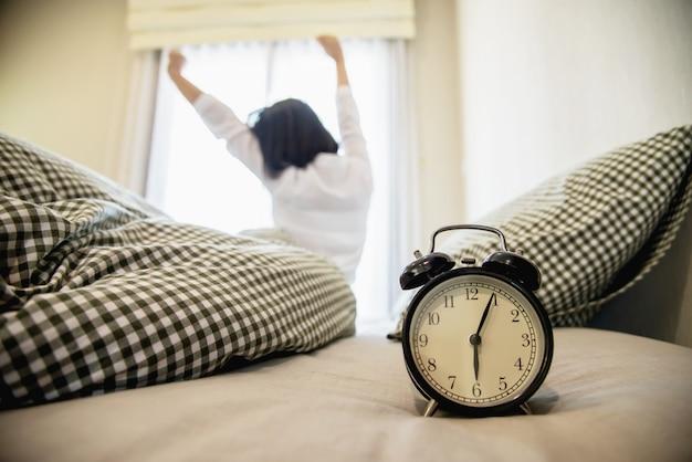 女性は新鮮な朝のために怠惰にストレッチ自分を目覚めさせる