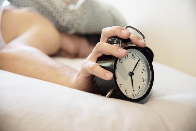 目覚まし時計を保持している眠そうな男