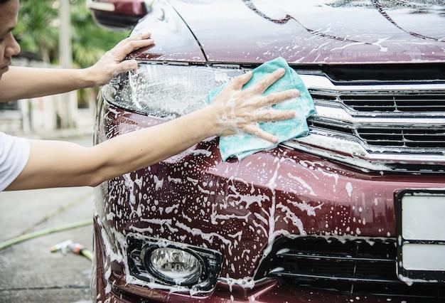 Человек моет машину с помощью шампуня