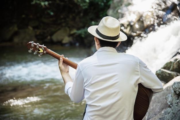 男は滝の近くにギターを弾く