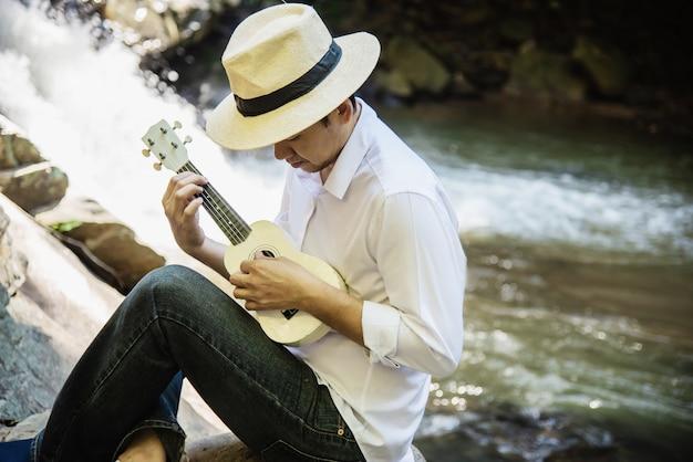 男は滝に新しいウクレレを弾く