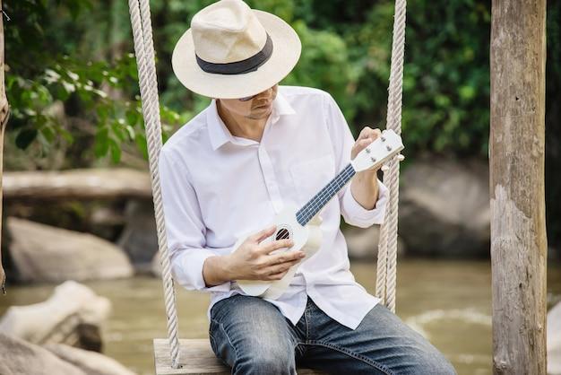 男は川に新しいウクレレを演奏