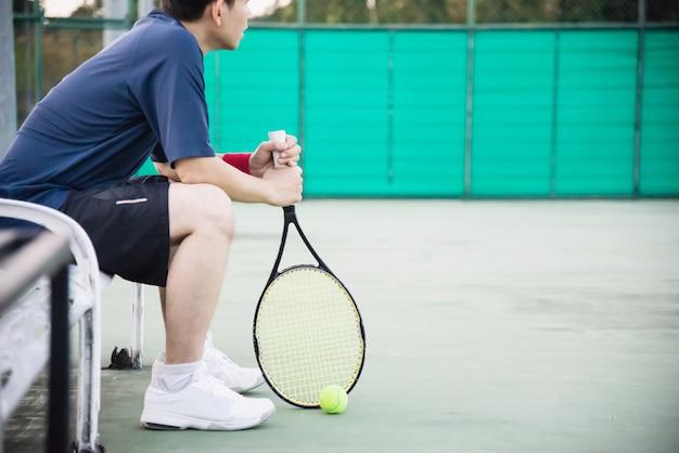 試合に負けた後に裁判所に座っている悲しいテニス選手