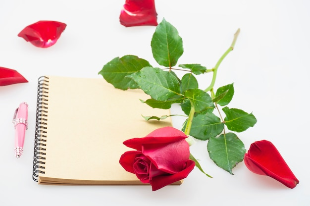 白い背景の上のノートと赤いバラとピンクのペン