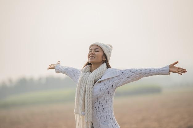 のどかな自然の中で楽しんで、自由を祝うと彼女の腕を上げる幸せな女