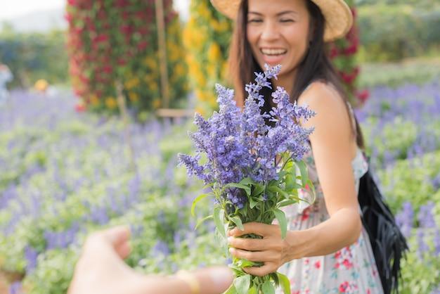 美しい中年のアジア女性の屋外のポートレート。花を持つフィールドで魅力的な女の子