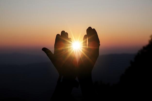 Духовная молитва вручает солнце сияет размытым красивым закатом