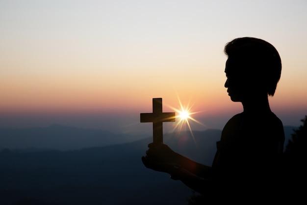 太陽の上の精神的な祈りの手がぼやけて美しい夕日と輝き