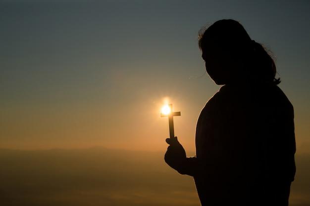 十代の少女の祈りとクロスを保持しています。平和、希望、夢の概念。
