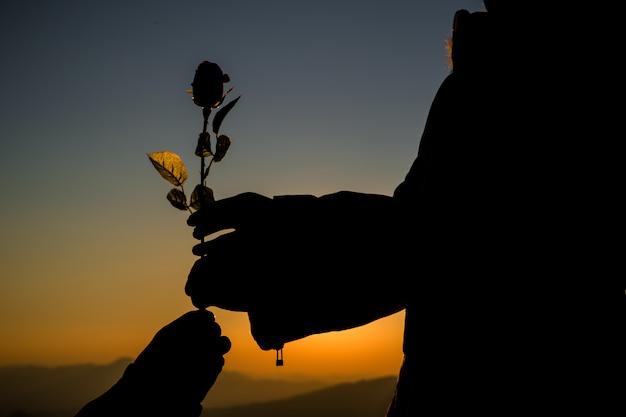 背景に日没時のスカイラインの丘の上に保持しているカップルのシルエット