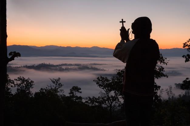 十字架を持っている人間の手のシルエット、背景は日の出です